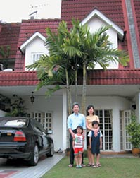 Семья Ли возле своего дома в пригороде Куала-Лумпура.